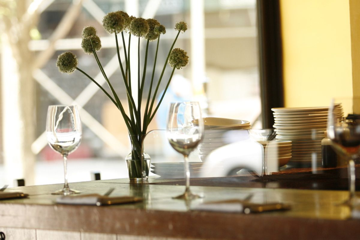 A restaurant countertop with wine glasses and a plant vase