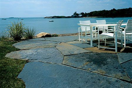 Patio made out of goshen stone next to a lake.