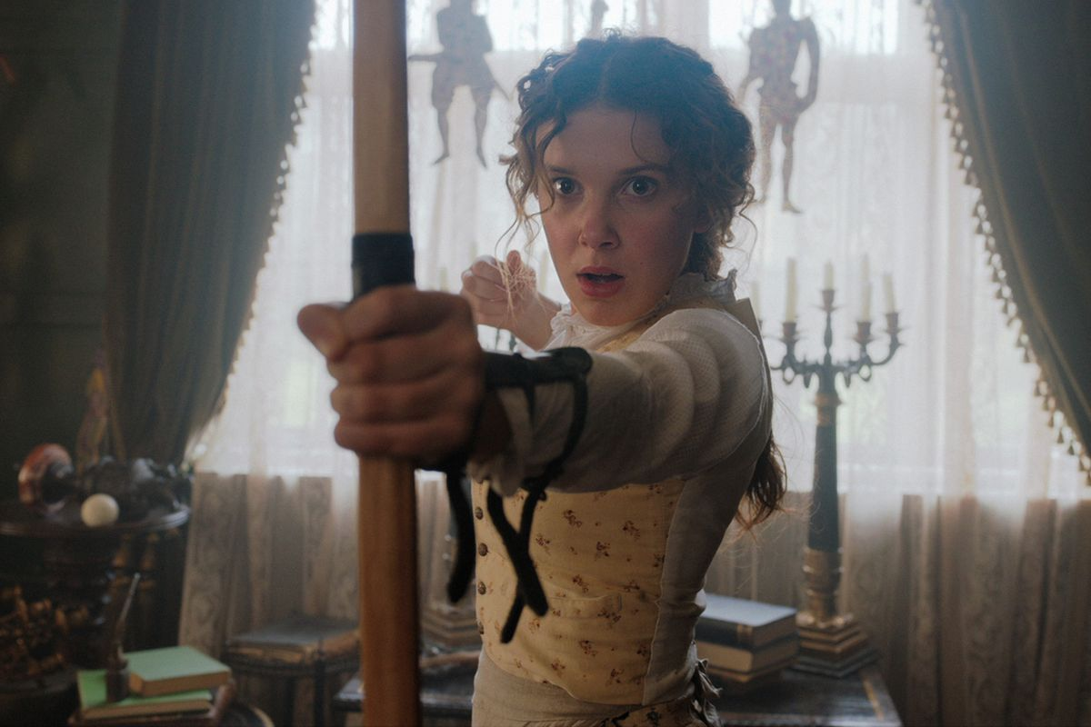millie bobby brown as enola, with a bow and arrow