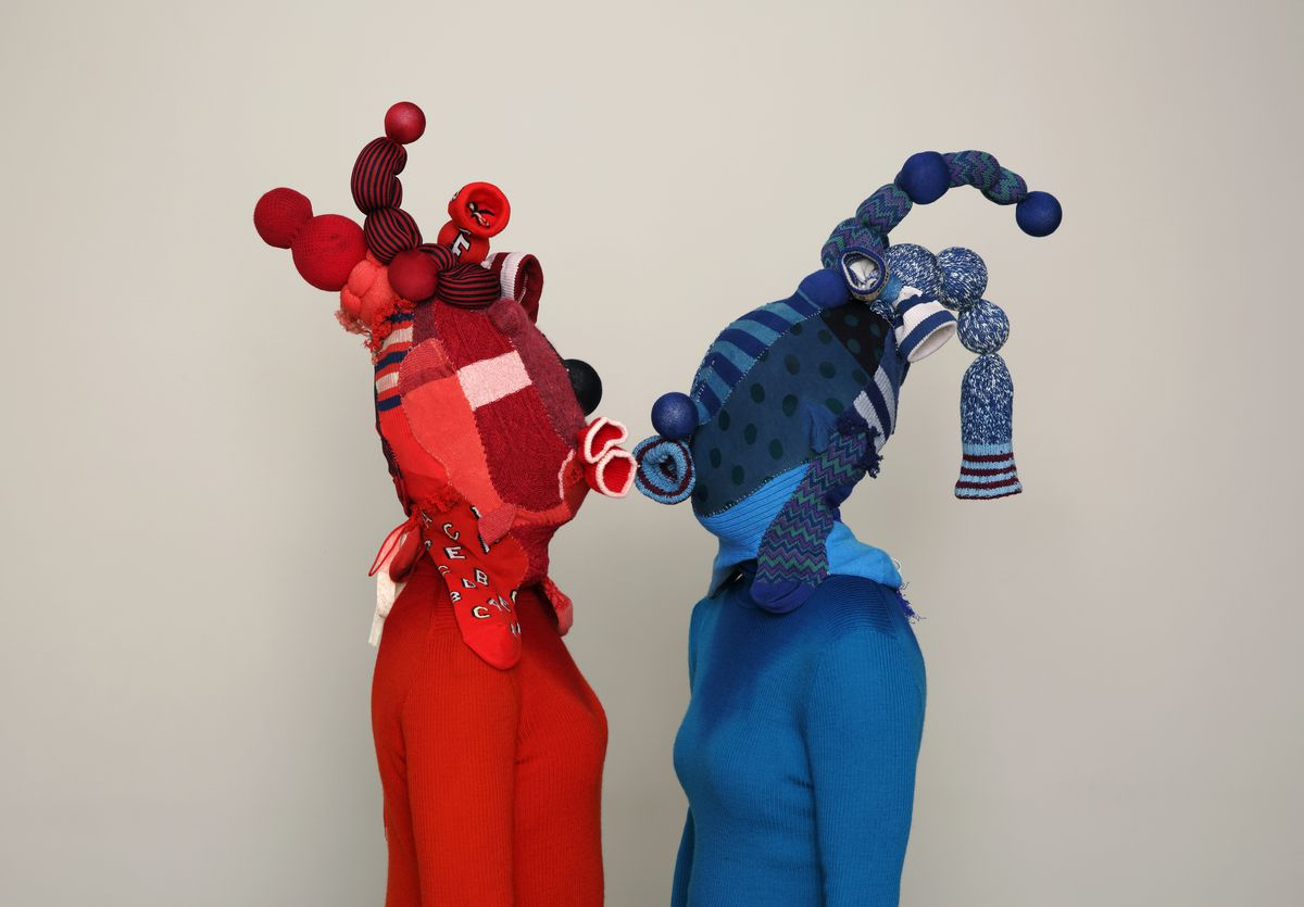 Photo of a couple covered head to toe in odd protective masks and outfits.