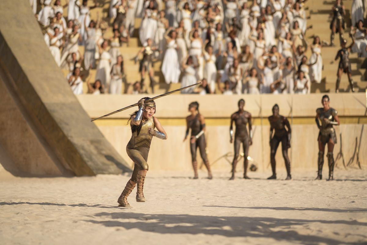 A young Diana runs in an ancient arena with a spear as other Amazons cheer her on