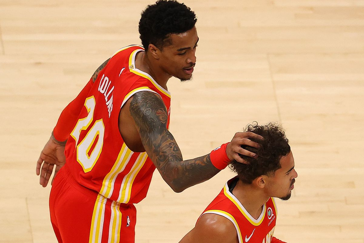 John Collins of the Atlanta Hawks reacts with Trae Young during the first half against the Detroit Pistons at State Farm Arena on December 28, 2020 in Atlanta, Georgia.
