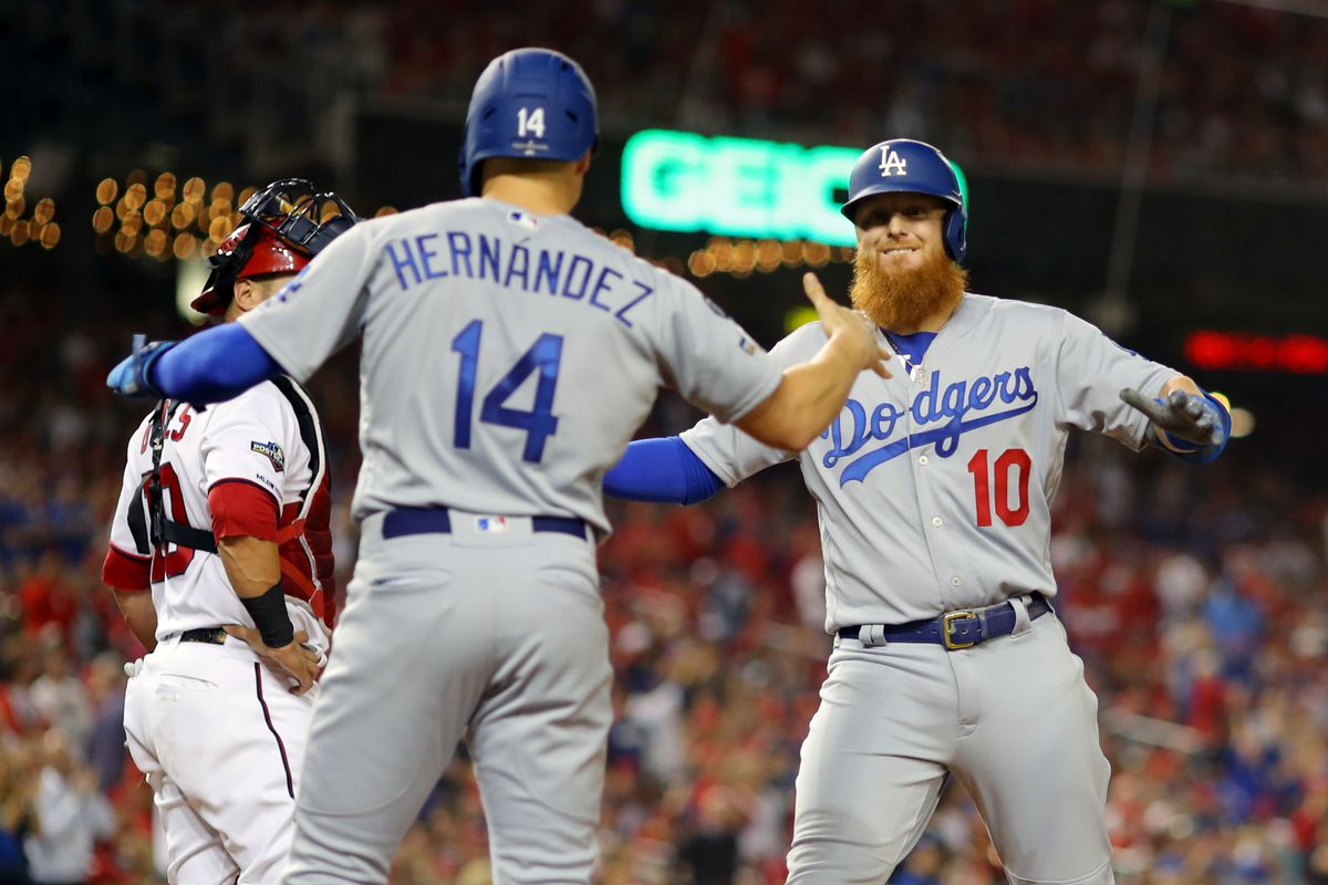 Justin Turner #10 of the Los Angeles Dodgers is greeted by Enrique Hernandez #14 after hitting a three-run home run during Game 3 of the NLDS between the Los Angeles Dodgers and the Washington Nationals at Nationals Park on Sunday, October 6, 2019 in Washington, District of Columbia.