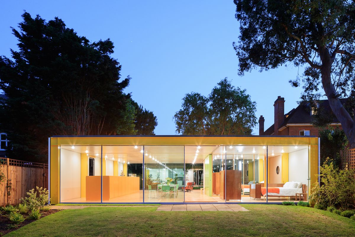 Night shot of low, flat box with walls of sliding glass doors and yellow frame set on a grassy site.