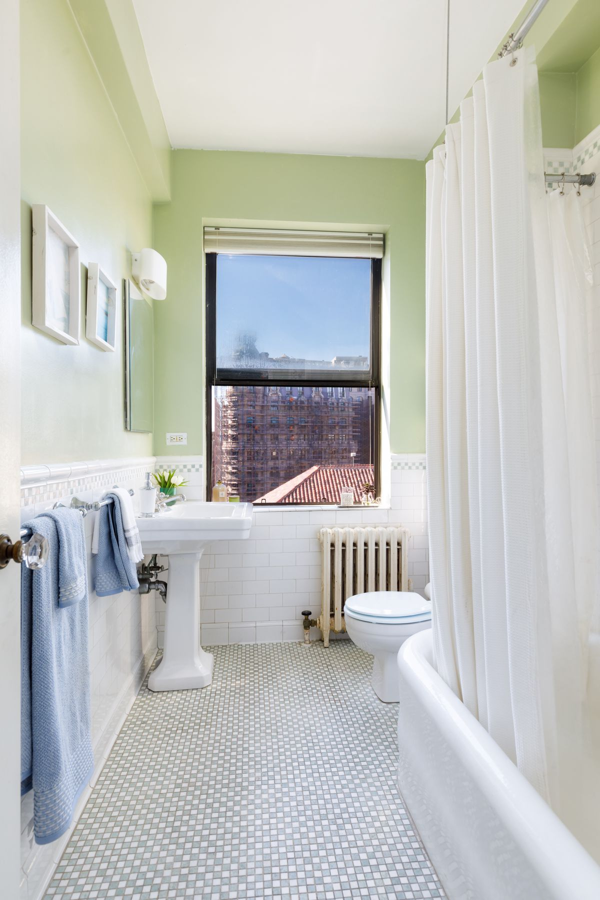 A bathroom with light green walls, a mosaic floor, and a window.