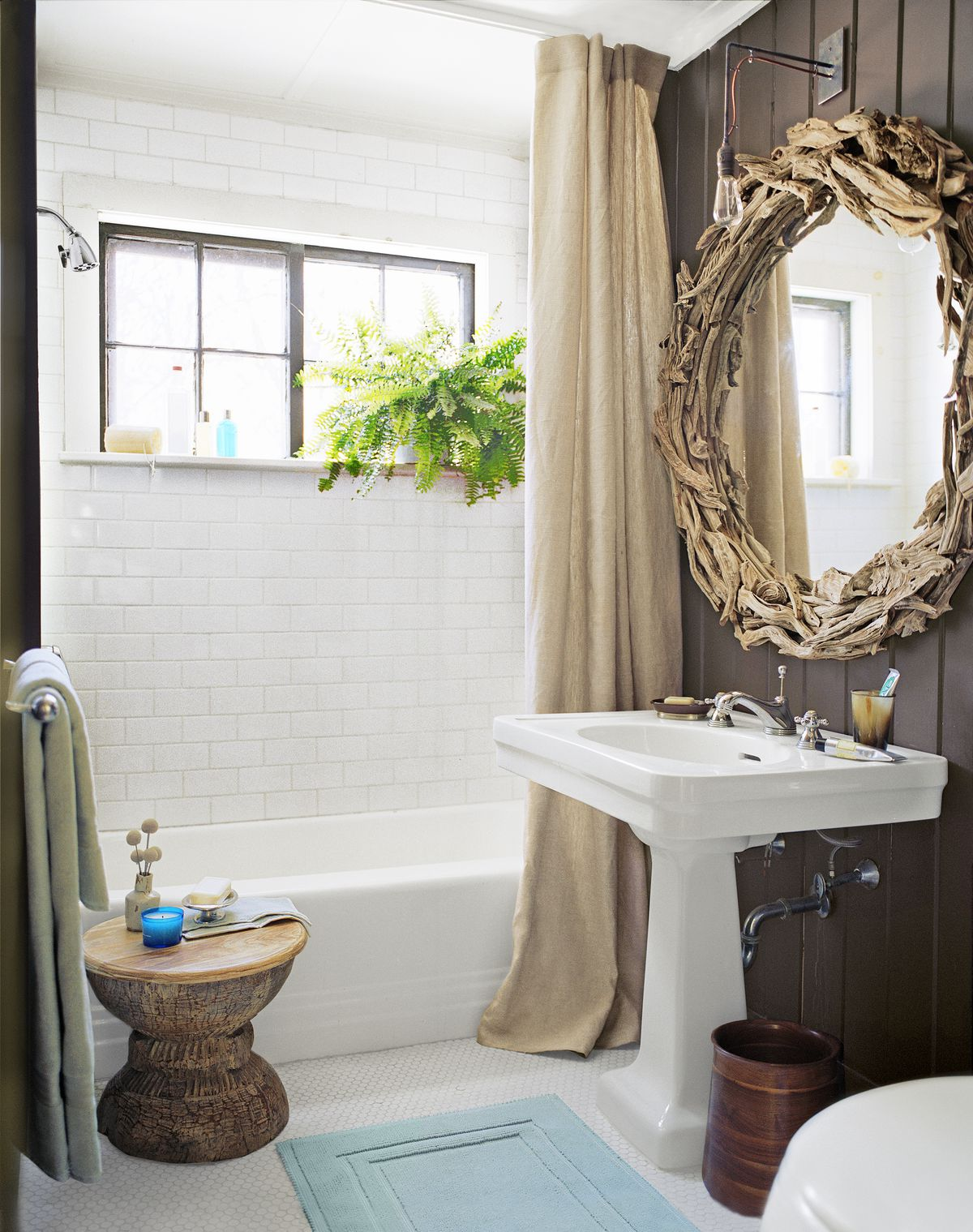 Brown curtain hanging from ceiling in front of bathtub.