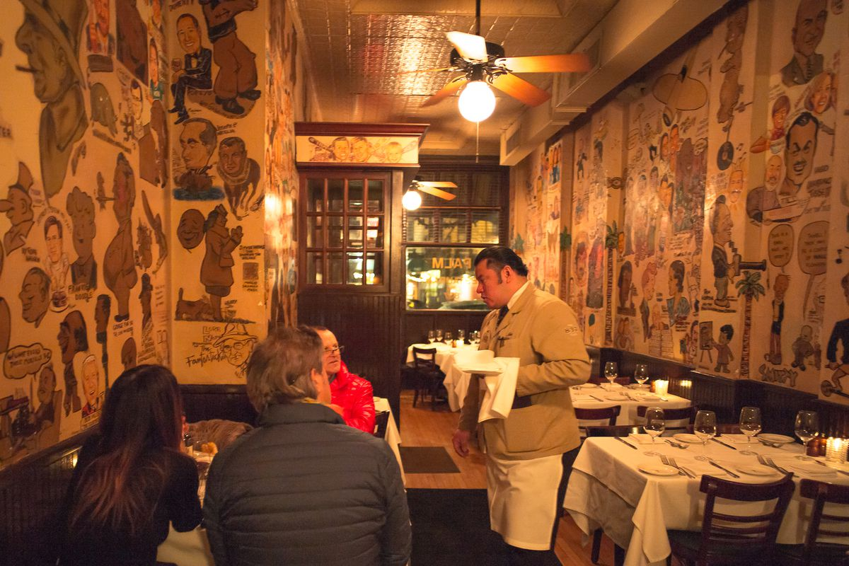 The original Palm, with caricatures on the walls and a waiter at a table.