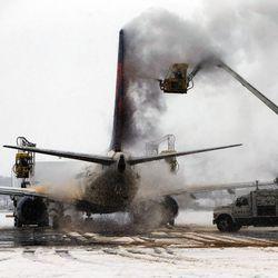 A jet is de-iced at Salt Lake City International Airport, Thursday, Dec. 19, 2013.