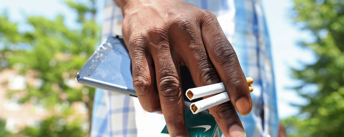 A hand holding a cellphone and two cigarettes.