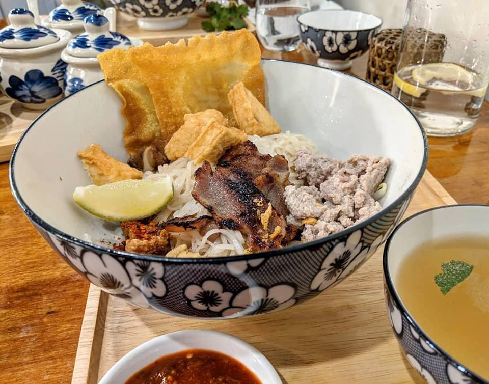 Big bowl of noodles, pork, fried wontons, and other ingredients, served next to a small bowl of plain chicken broth.