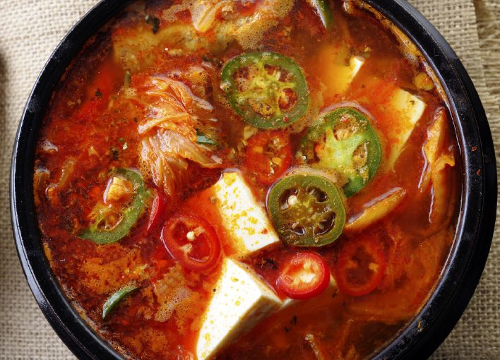A small black bowl of bright red soup with kimchi