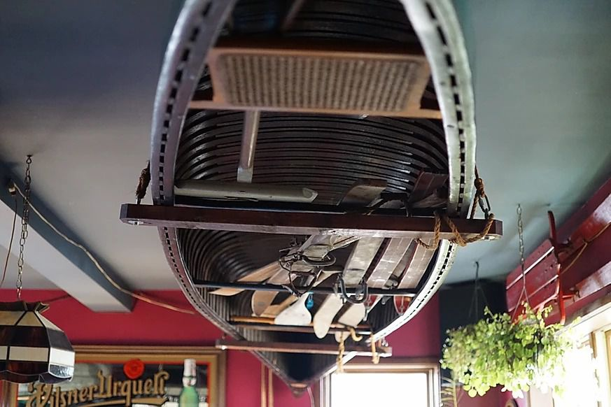 Upside down rowboat attached to the ceiling of a restaurant. A bit of the restaurant is visible, including bright red walls and a mirrored Pilsner Urquell sign.