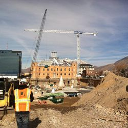 A construction worker returns from lunch on Wednesday, Nov. 27, as crane moves a load from the west side to the east side of the Provo City Center Temple construction site.