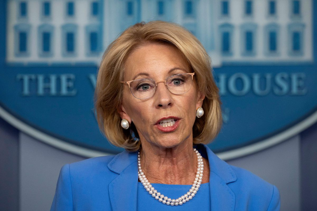 Photo of Betsy DeVos in pearls and blue shirt