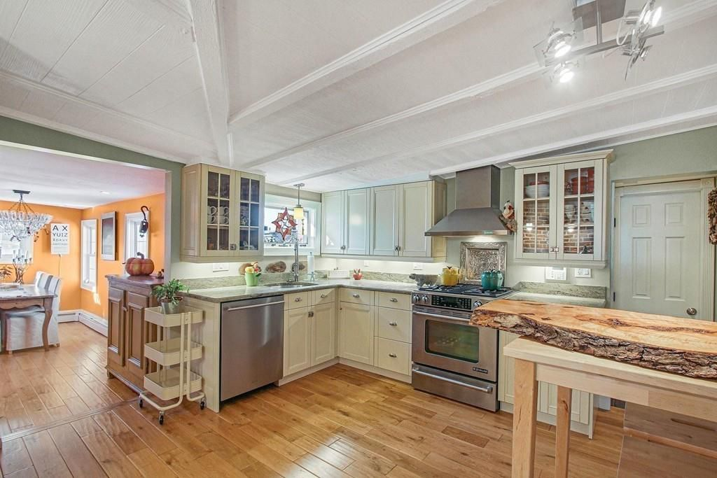 A spacious, open kitchen with counters meeting at a right angle and a long table with a log-like cutting board on it.
