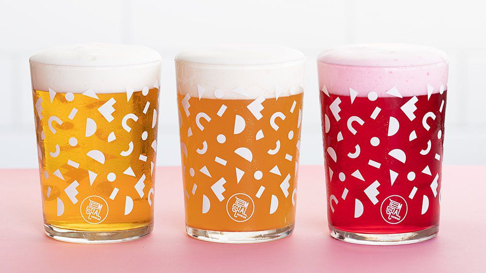 Three glasses of beer in various colors sit side by side in decorative glasses