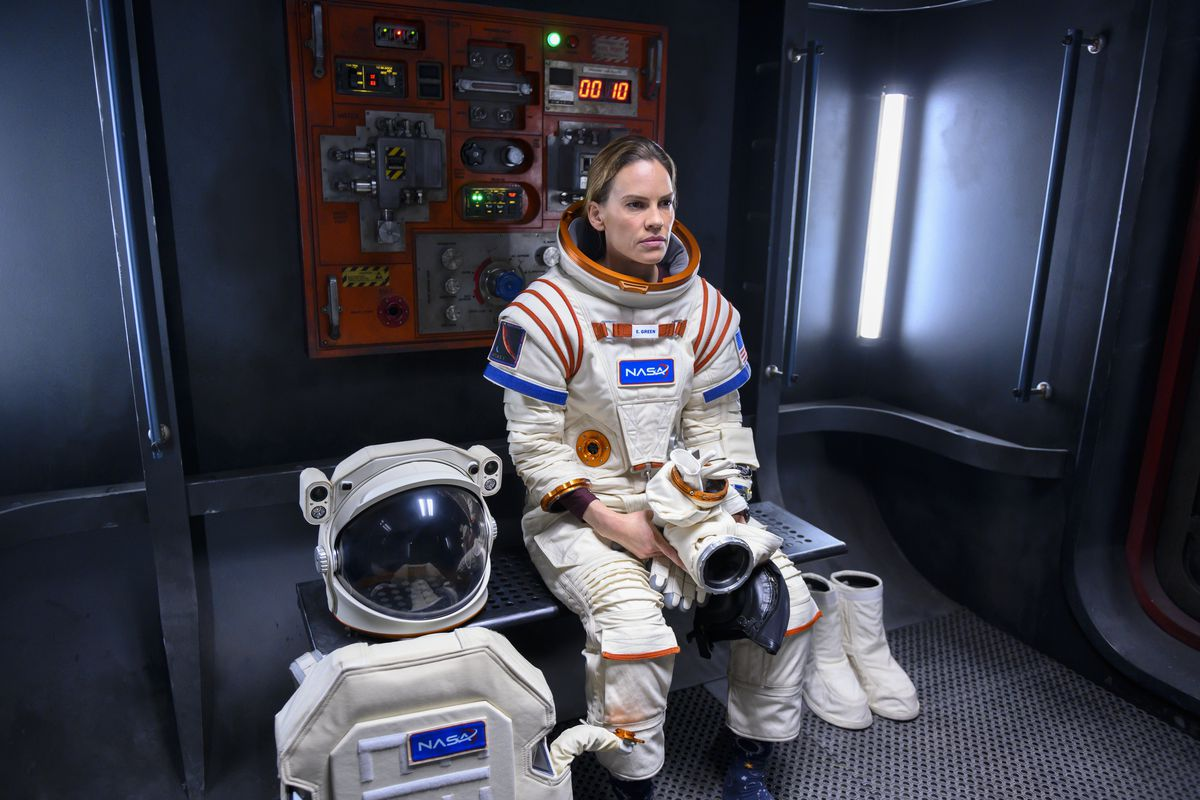 Hilary Swank, in full spacesuit, sits staring on a bench in Netflix's space series Away.