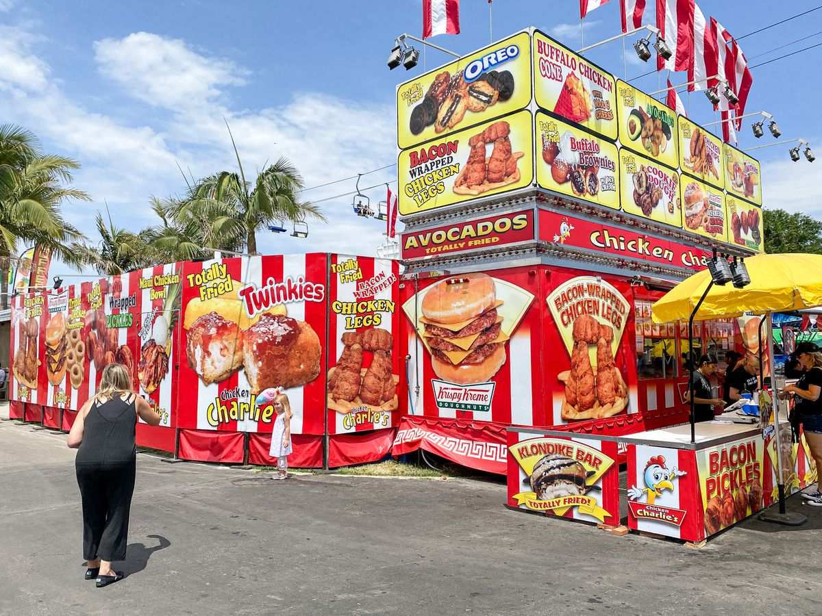 Two customers line up to take photos next to a giant image of a doughnut burger at a county fair.