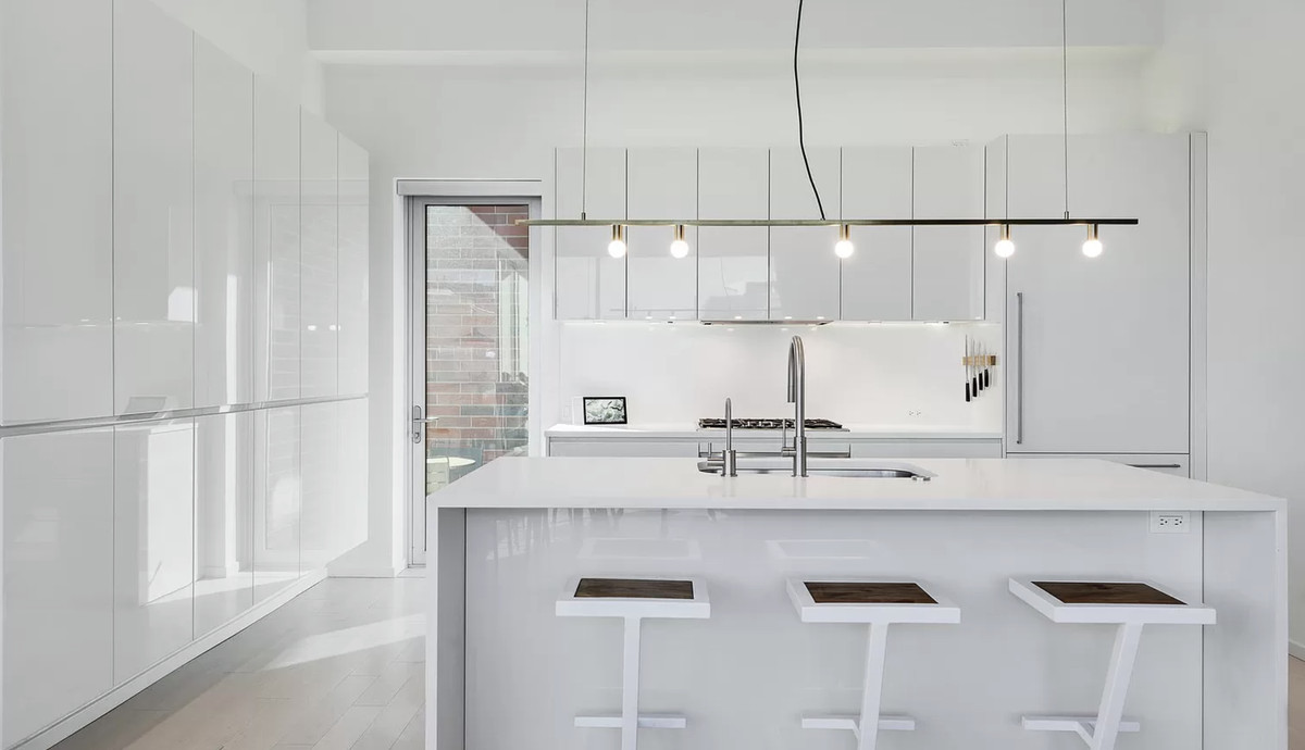 The kitchen features all white cabinets, a white island with three stools, and a bare bulb light fixture.