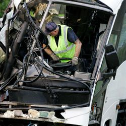 FILE - In this Aug. 8, 2008 photo, an emergency worker wrestles with the steering wheel on a wrecked bus that several people died on in an early morning accident on U.S. 75 North bound in Sherman, Texas. Months after their state-certified vehicle inspection station was cited by federal authorities for failing to notice defects in a bus that crashed in North Texas, killing 17 passengers, brothers Alam and Cesar Hernandez shuttered their firm. But that didn't mean they were out of the vehicle inspection business.