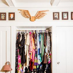 The colorful closet, festooned by wings Amanda made and wore for Halloween one year, which is surrounded by her fiance Ben Walker's art. Also note the LV mini.