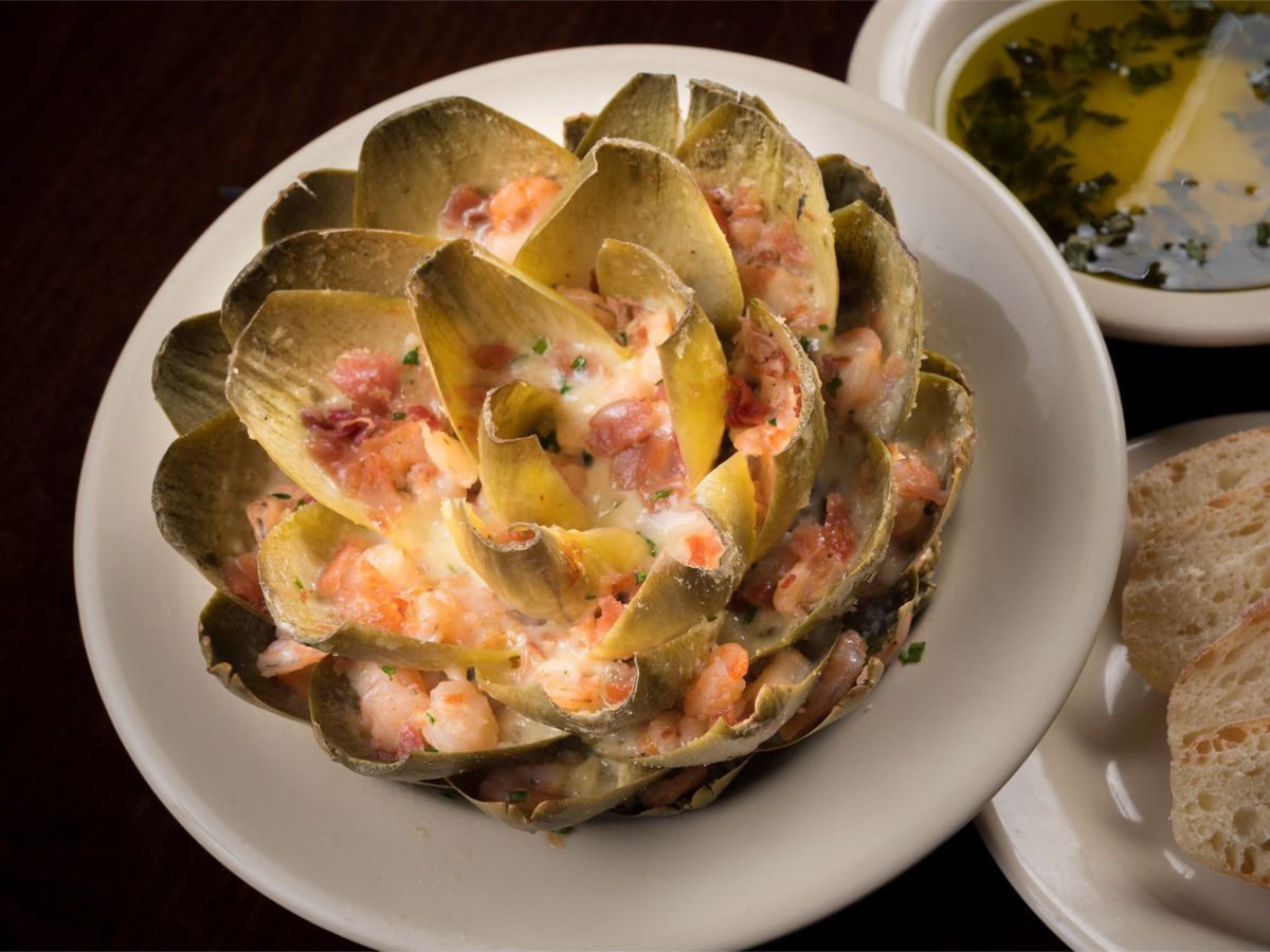 A large artichoke, its petals spread and stuffed with creamy shrimp sauce, beside a plate of bread and olive oil