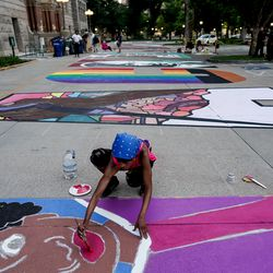 Katlyn Addison assists in putting the final touches on one of two letters by lead artist Liz Lambson on a Black Lives Matter mural outside the City-County Building in Salt Lake City on Tuesday, Aug. 4, 2020.