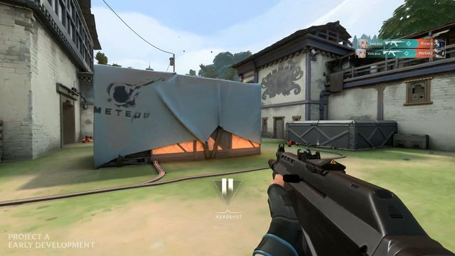 A player in Riot Games' Project A shooter stands with a gun in hand aiming at a box