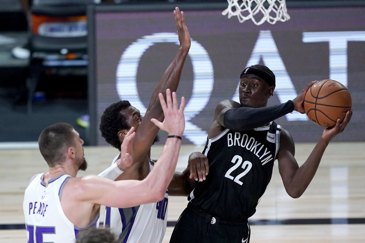 Caris LeVert of the Brooklyn Nets looks to pass the ball as Alex Len and Harrison Barnes of the Sacramento Kings defend during the second half of an NBA basketball game at the ESPN Wide World Of Sports Complex on August 7, 2020 in Lake Buena Vista, Florida.