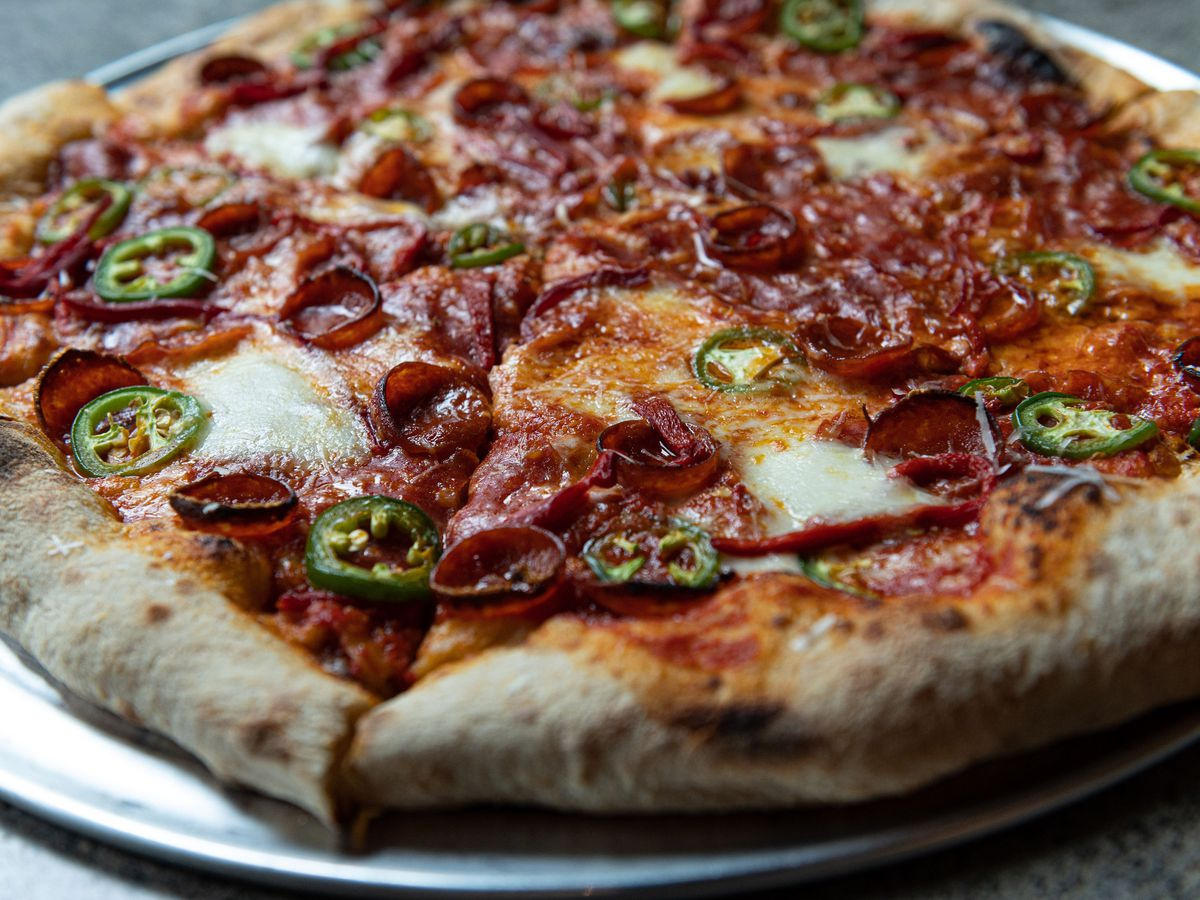 A sourdough crust pizza from Pizza Thief comes topped with sliced peppers and pepperoni
