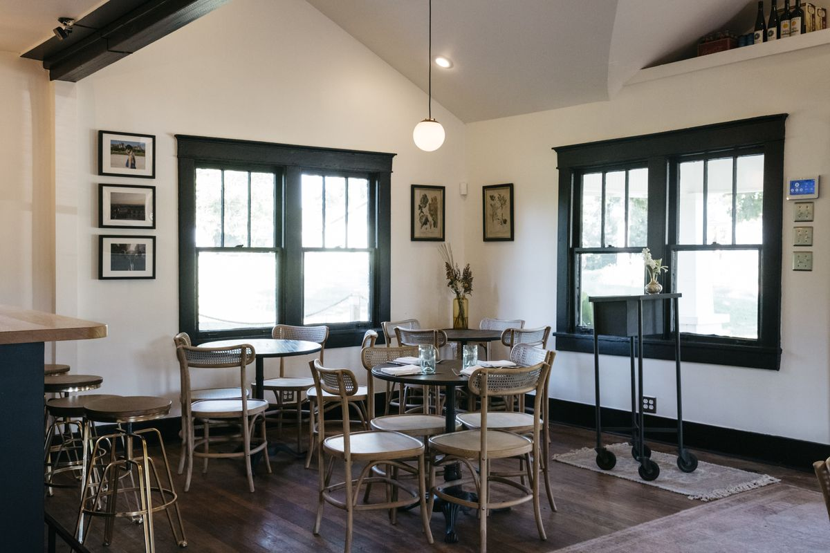 Upon entering, a seating area to the right with wooden chairs and black top tables, art hanging on walls