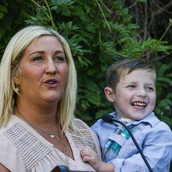 Wynter Abby Johnson, left, the mother of Dash Johnson, 4, a patient at Primary Children's Hospital, holds her son as she speaks during the reopening of the Angel Garden at the hospital in Salt Lake City on Monday, Aug. 1, 2016. The redesigned garden includes more than 1,000 new plants and trees, as well as legacy monuments, including the Butterfly Angel statue, a commissioned 5-foot bronze. Dash's family spearheaded renewal project.