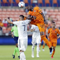 Houston Dynamo defender Teenage Hadebe (18) collides with Real Salt Lake forward Bobby Wood (7) as he goes for a head ball during the first half of an MLS soccer match Saturday, July 31, 2021, in Houston.