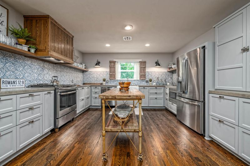 A kitchen with a cart as island, wood floors, gray cabinets, and light blue tile.