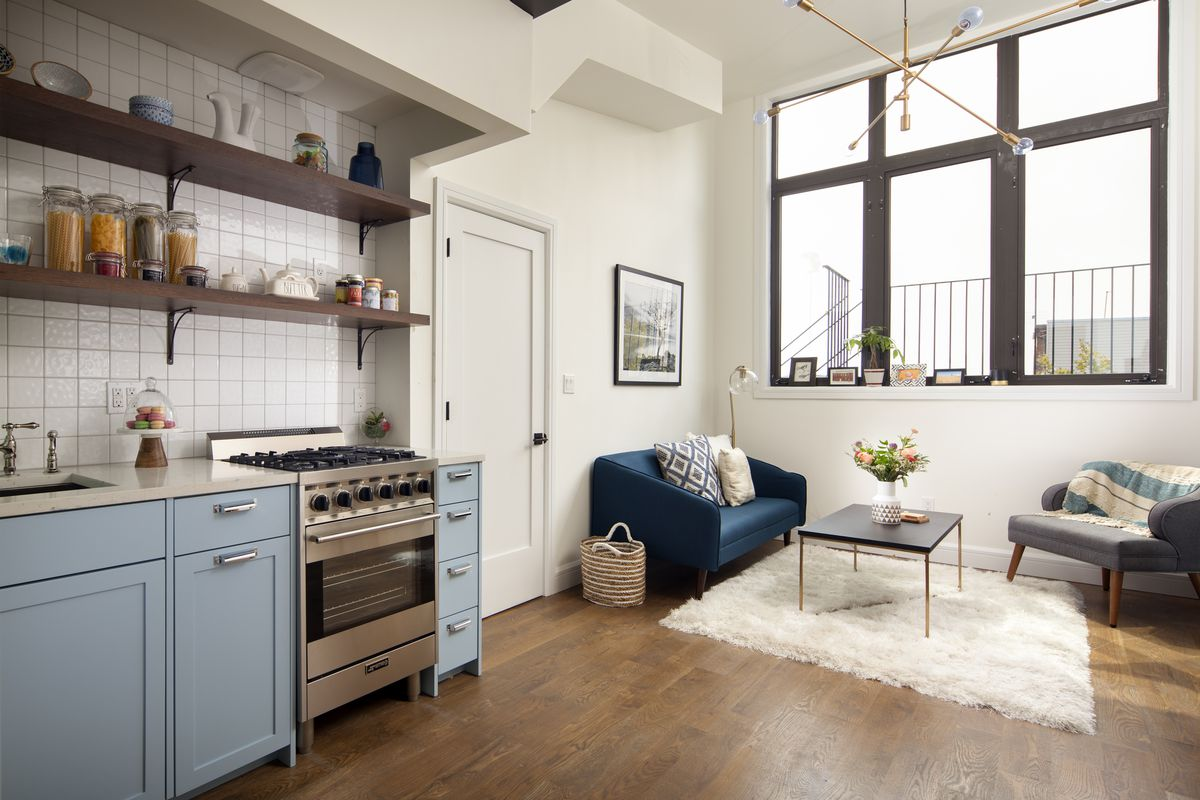 A small kitchen with light blue cabinetry and a living room with a dark blue couch, a beige rug, and a large window.