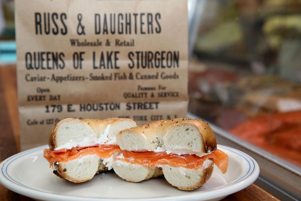 Pieces of salmon jut out of a bagel sandwich sliced in half, that's placed on a white cermaic plate. A sign for Russ & Daughters hangs in the background.