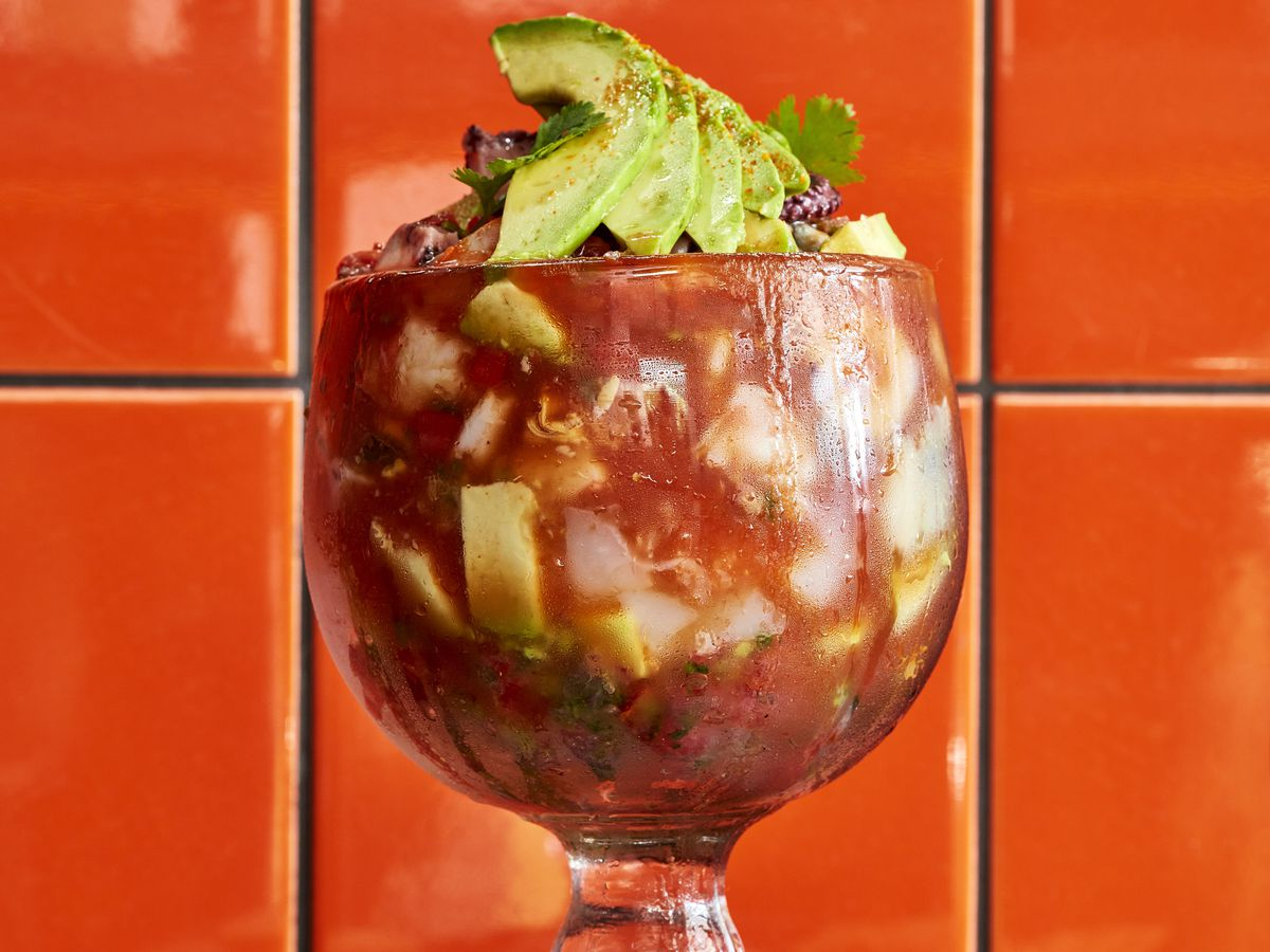 A goblet of ceviche against a red tiled background.