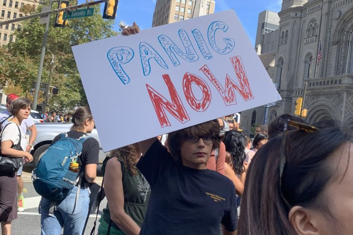 """A """"Panic now"""" sign reflects the urgency of young people who are worried about the future of the Earth."""
