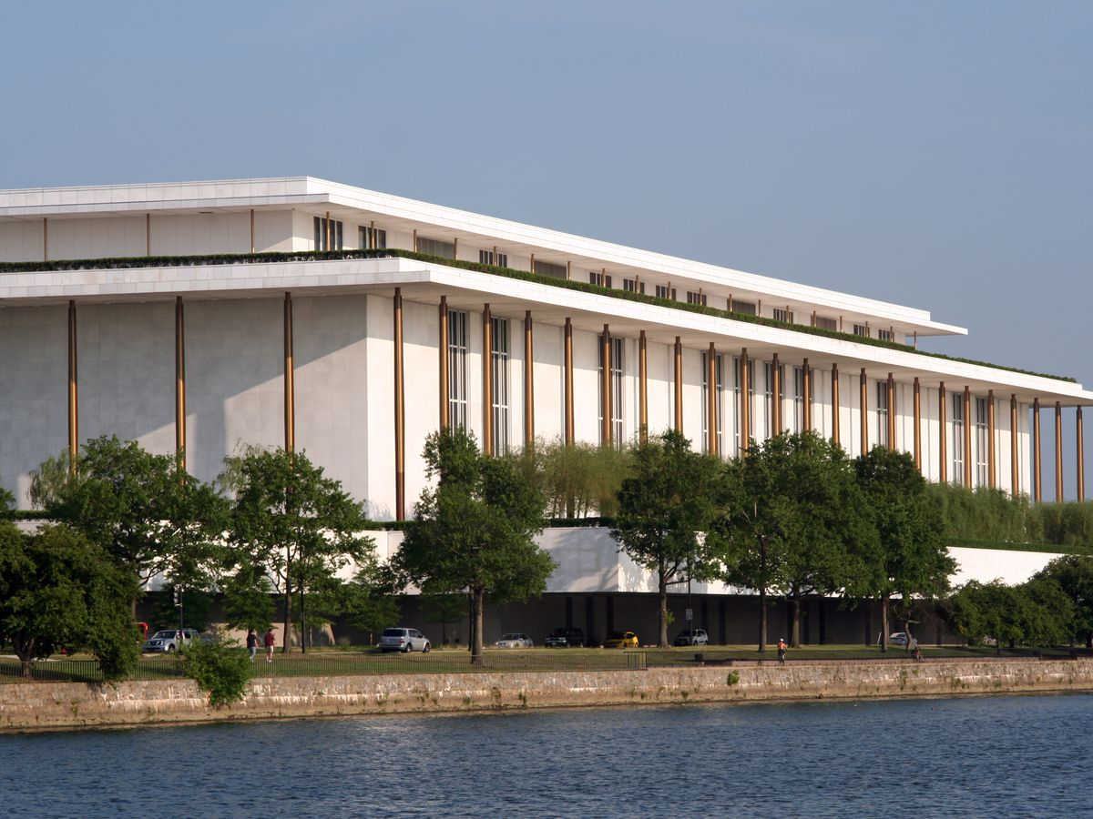 The exterior of the John F. Kennedy Center for the Performing Arts. The facade is white and there are trees in front.
