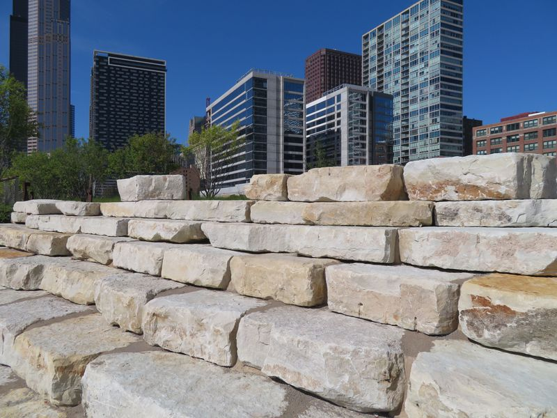 Stepped blocks on limestone are arranged in a semicircle. Bush and trees are visible on the side and high-rise building beyond.
