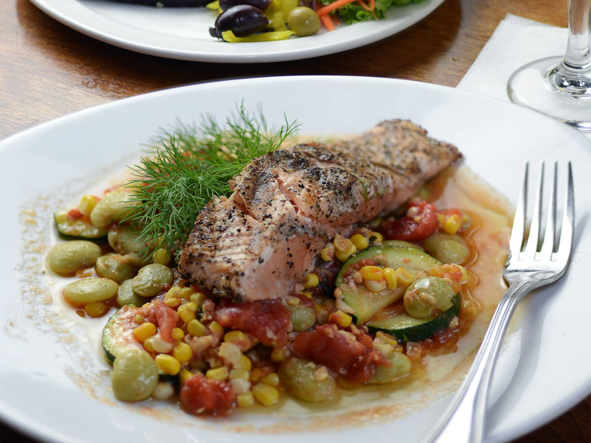 Grilled salmon and sweat potatoes sit atop a bed of succotash made with various summer vegetables and lima beans. A spring of bright green dill garnishes the dish.