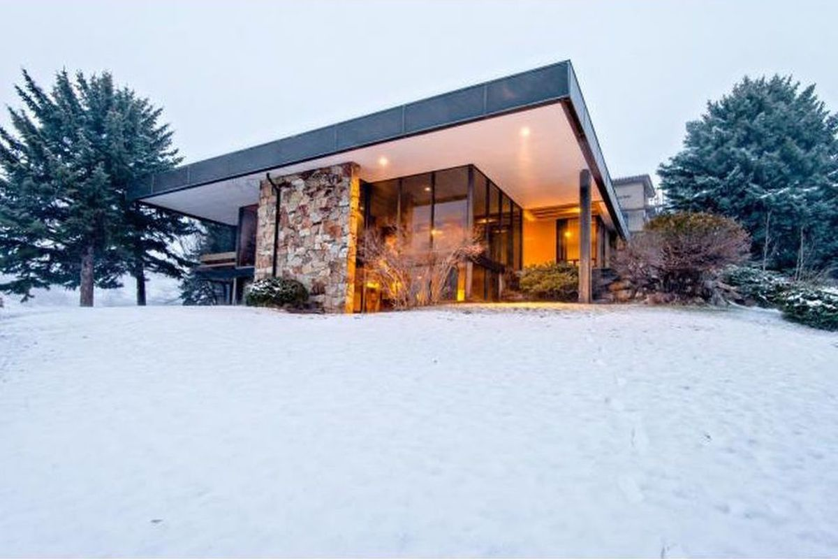 Exterior shot from the snow-covered backyard of flat, cantilevering roof, floor-to-ceiling windows, and large stone column.