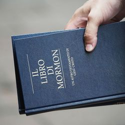 Elder Samuel Nagliati, a missionary for The Church of Jesus Christ of Latter-day Saints, holds a Book of Mormon as he and his companion make contacts in Bologna, Italy, on Thursday, Sept. 16, 2021.