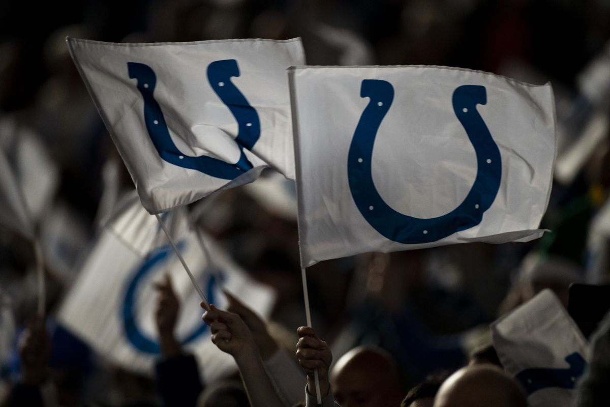 """Indianapolis Colts fans wave flags bearing the team""""u2019s logo before the game against the Tennessee Titans at Lucas Oil Stadium on December 1, 2019 in Indianapolis, Indiana. Tennessee defeats Indianapolis 31-17."""