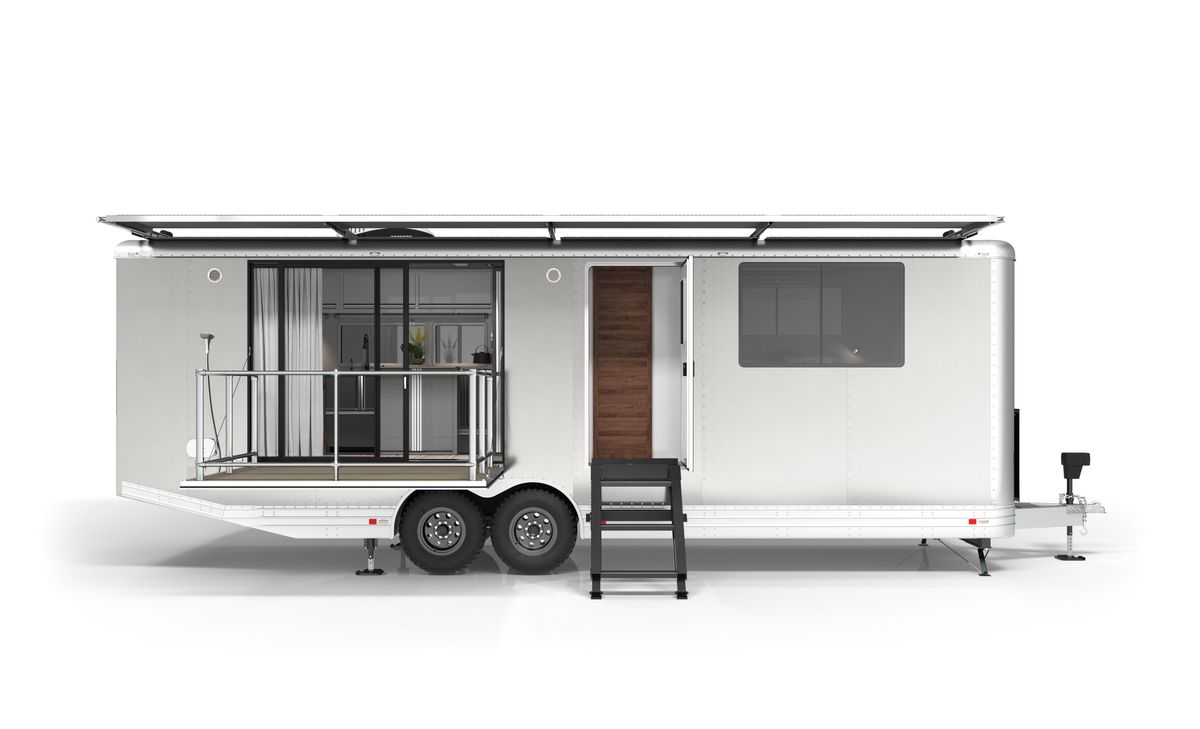 An aluminum travel trailer features a drop-down patio, stairs to an open door, and a shade awning.