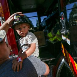 Ryan You places a plastic fire helmet on his son, Ronan, 2, while the Salt Lake City Fire Department shows off its two new ladder trucks at Smith's Ballpark in Salt Lake City on Tuesday, June 27, 2017.