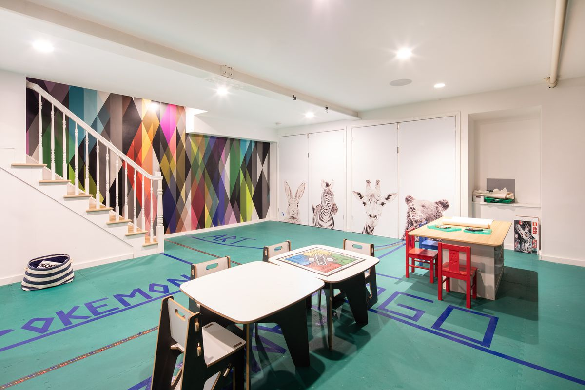 An underground rec room features graphic wallpaper lining the stair wall and green foam flooring.