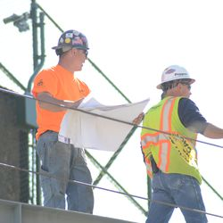 4:02 p.m. Contractor checking blueprints behind the center field scoreboard -
