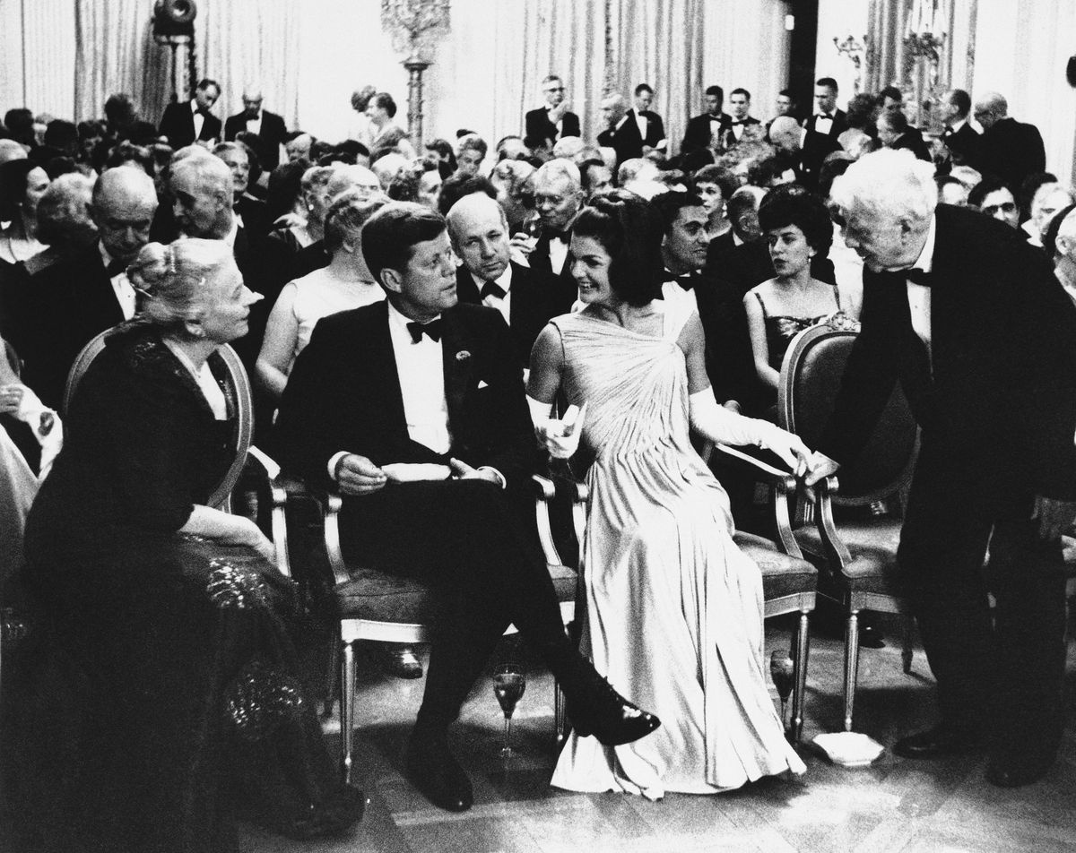 President John F. Kennedy sits with first lady Jacqueline Kennedy as poet Robert Frost, right, and Pearl Buck, left, exchange greetings in the East Room of the White House in 1962. A year earlier, Frost spoke at President Kennedy's inaugural.
