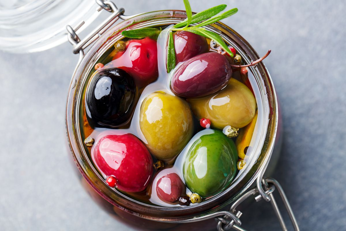 Colorful olives and a rosemary sprig sitting in olive oil in a lidded glass jar.